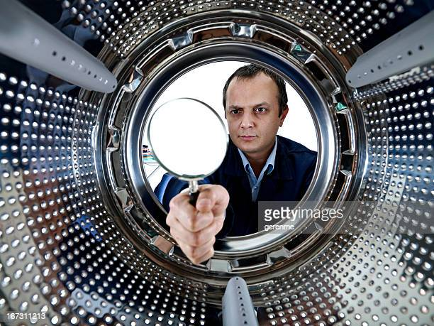 Repairman looking in the washer with Magnifying Glass