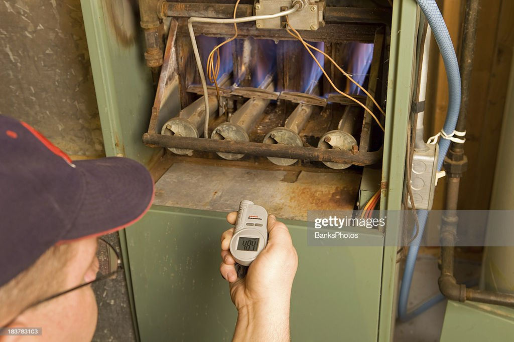 Repairman with Digital Infrared Thermometer Checks Gas Furnace Output Temperature : Stock Photo