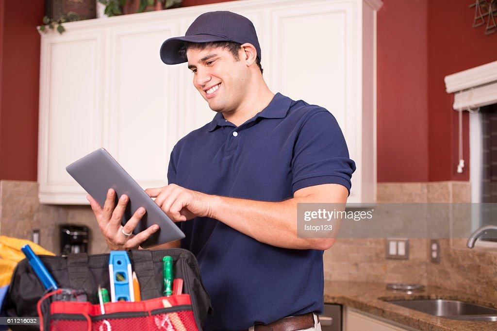 Repairman working inside customer's home. : Stock Photo