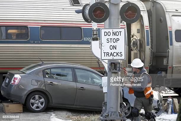 A repairman works on the railroad crossing signal on Brighton Avenue Police say this Nissan Sentra collided with Amtrak's Downeaster after trying to...