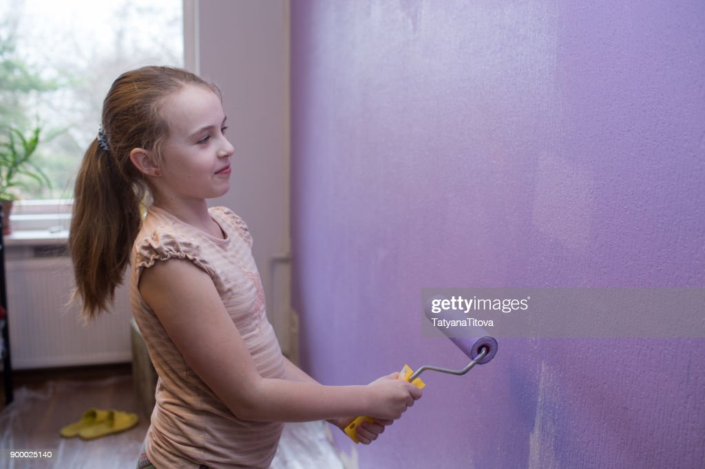 Repairs in the apartment. Girl paints the wall with ultraviolet paint - trend 2018 : Stock Photo