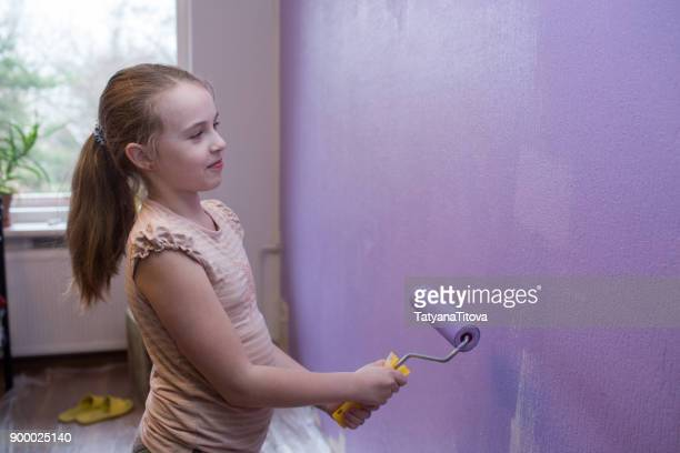 repairs in the apartment. girl paints the wall with ultraviolet paint - trend 2018 - petite teen girl stock photos and pictures