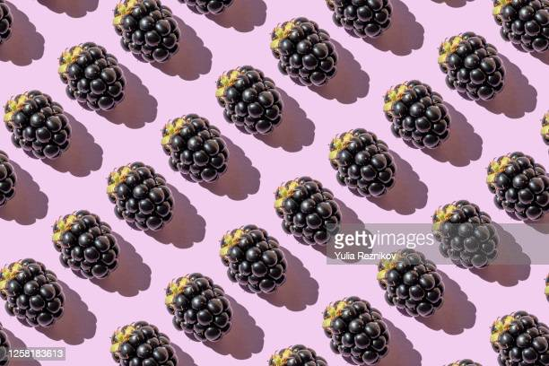 repeated blackberries on the purple background - blackberry fruit stock pictures, royalty-free photos & images