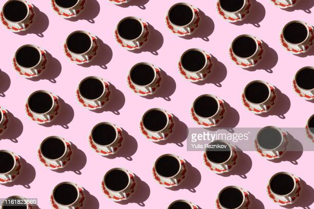 repeated cup of coffee on pink background - caffeine stock pictures, royalty-free photos & images
