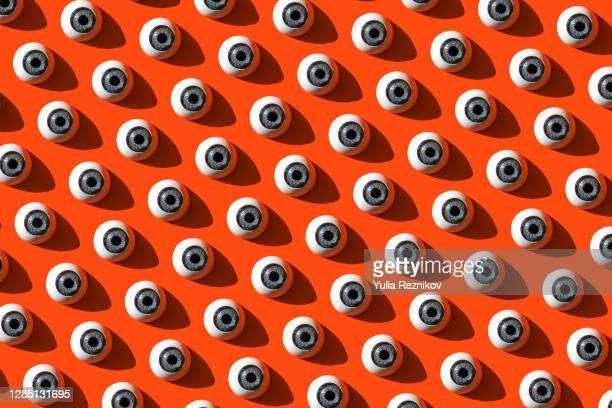 repeated eyes on the red background - bevrijden stockfoto's en -beelden