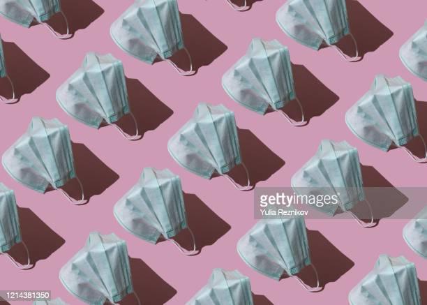repeated face mask on the pink background - ansteckende krankheit stock-fotos und bilder