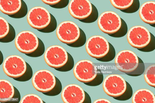 repeated grapefruits on the green background - pattern stock pictures, royalty-free photos & images