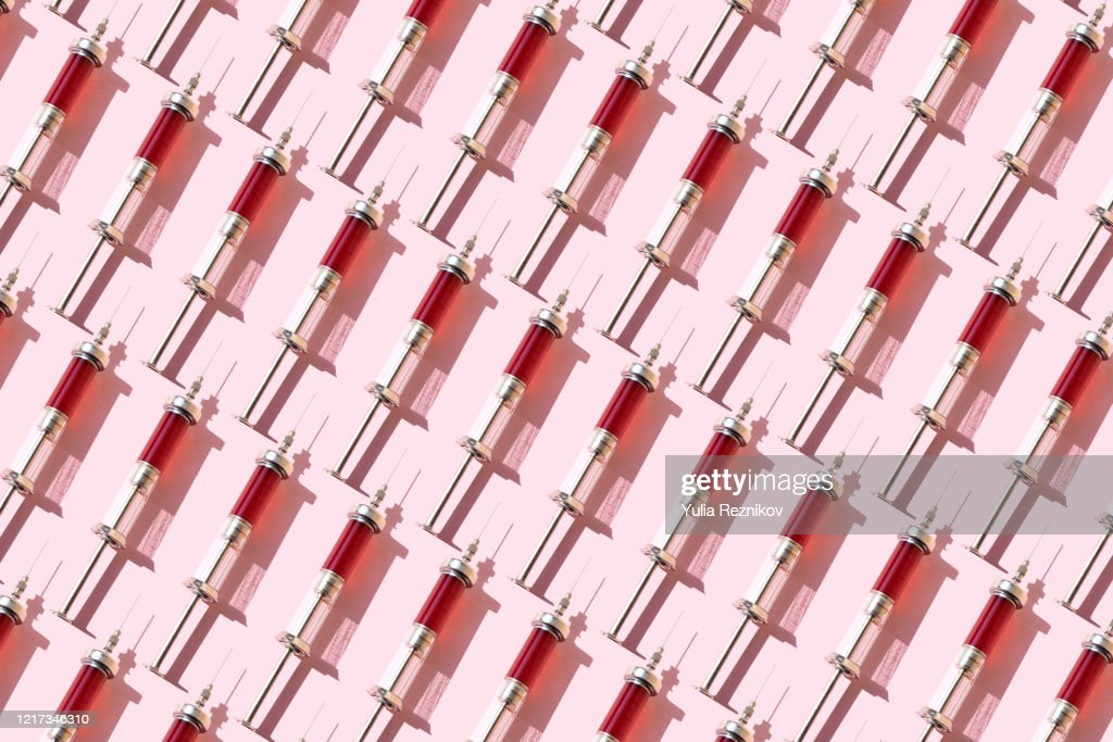 Repeated of blood in syringes on the pink background : Stockfoto