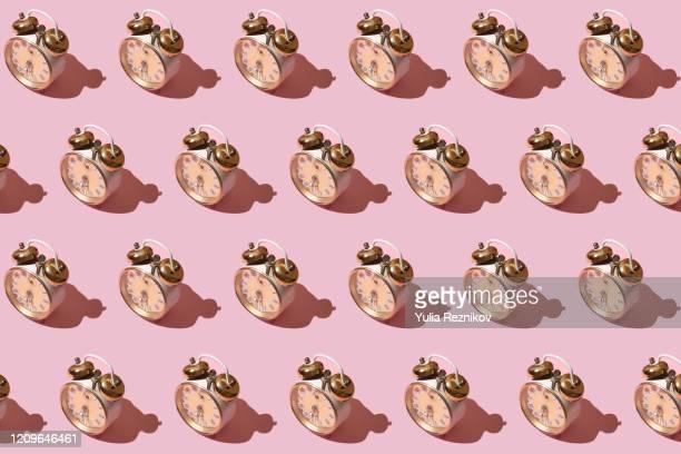 repeated old alarm clock on pink background - repetição conceito - fotografias e filmes do acervo