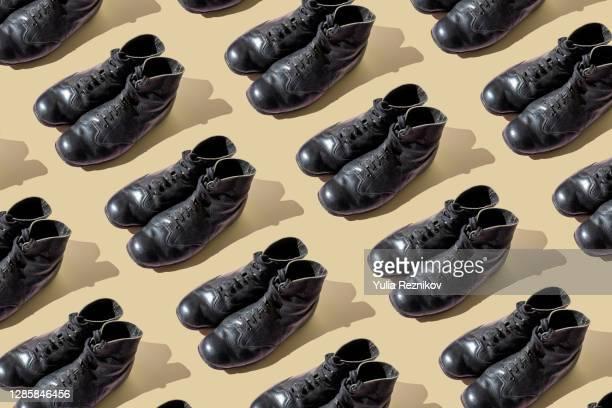 repeated old black shoes on the beige background - leren schoen stockfoto's en -beelden