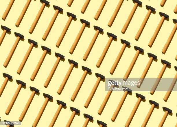 repeated old hammer on the yellow background - hammer stock-fotos und bilder