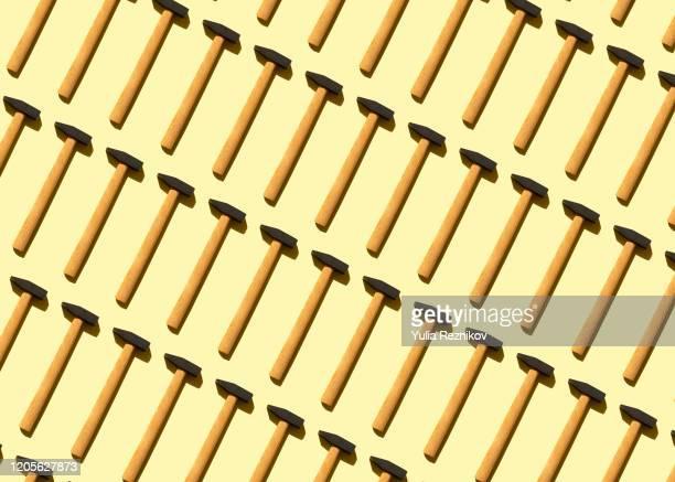 repeated old hammer on the yellow background - werkzeug stock-fotos und bilder