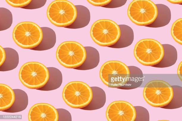 repeated orange on the pink background - orange fruit stock pictures, royalty-free photos & images