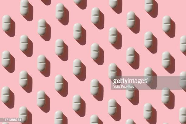 repeated pills on pink background - antibiotic stock pictures, royalty-free photos & images