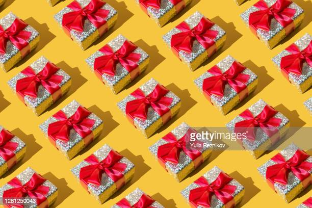 repeated silver gift box on the yellow background - holiday stock pictures, royalty-free photos & images
