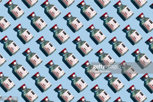 repeated vials with covid-19 vaccine on the blue background - dose stock pictures, royalty-free photos & images
