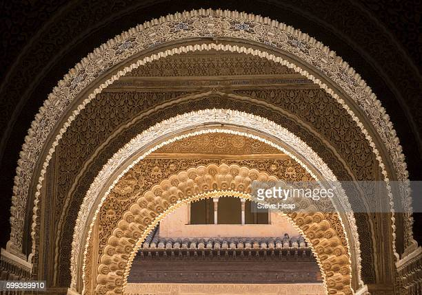 repeating series of arabic or islamic arches with courtyard of alhambra palace in granada spain - alhambra granada fotografías e imágenes de stock