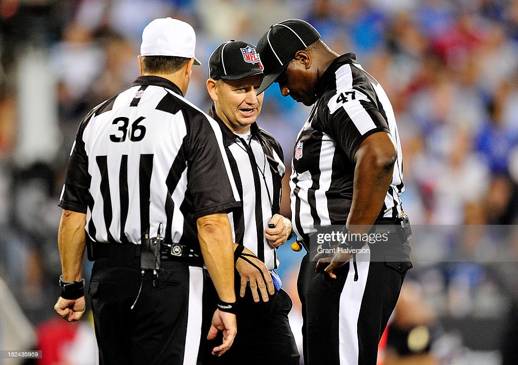 Replacement officials Robert Frazer #36, John Vachon #123, and Lemuel Hawkins #47 confer after throwing a penalty flag during a game between the New York Giants and the Carolina Panthers at Bank of America Stadium on September 20, 2012 in Charlotte, North Carolina. The Giants won 36-7.
