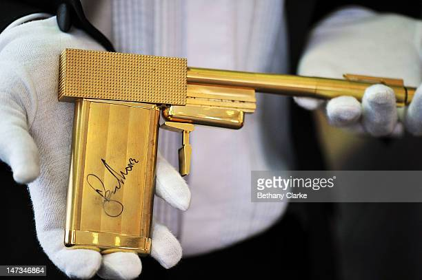 A replica gun from the 1974 James Bond movie 'The Man with the Golden Gun' autographed by Roger Moore The goldplated replica is offered with an...