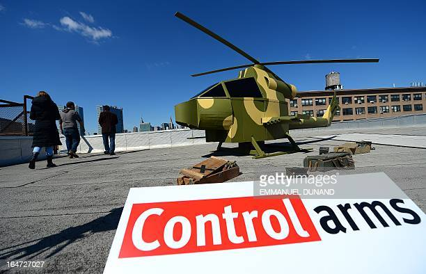 A replica of a camouflage militarystyle helicopter stands on a rooftop across Manhattan's skyline and the United Nations headquarters during a...