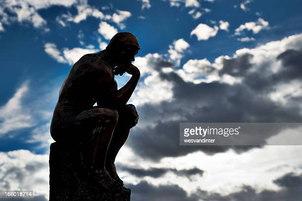 Replica of Rodin's The Thinker with sky background