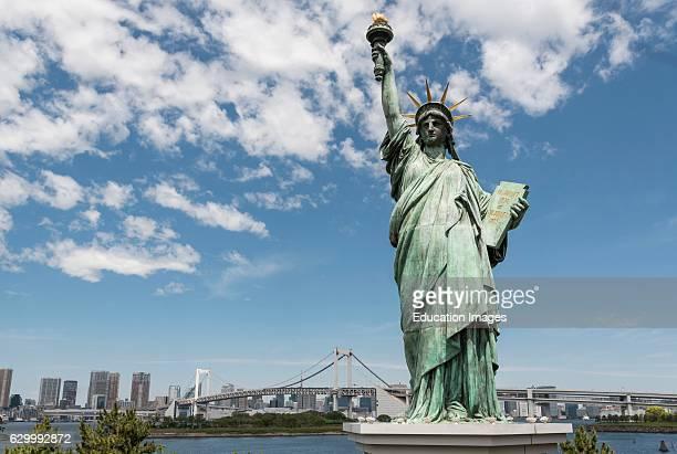 Replica of Statue of Liberty with rainbow Bridge Odaiba Seaside Park Tokyo Bay Japan