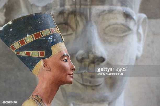 A replica of the bust of Nefertiti stands in front of a the replica of the a Sphinx head at the Replica Workshop of the National Museums of Berlin in...