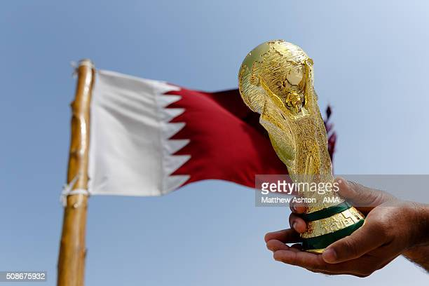 Replica of the FIFA World Cup Trophy in front of the maroon and white coloured flag of Qatar at the Al Zubarah Fort, a UNESCO World Heritage Site, in...