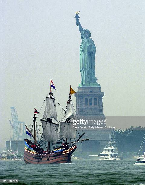 A replica of the Half Moon the ship that took Henry Hudson up the river which now bears his name sails past the Statue of Liberty in New York Harbor...