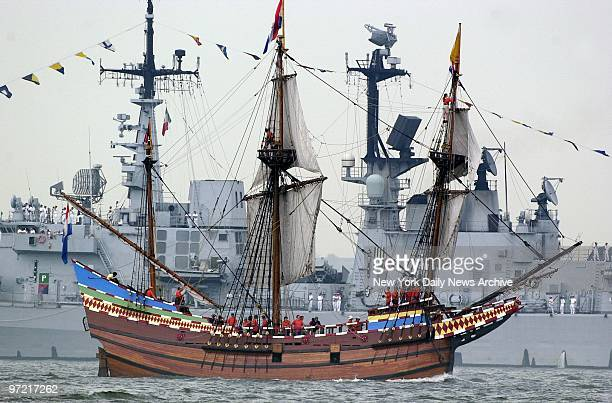 A replica of the Half Moon the ship that took Henry Hudson up the river which now bears his name sails past a modern warship during OpSail 2000