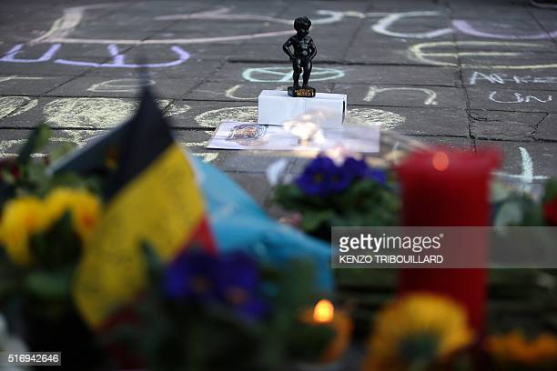 A replica of the Manneken Pis statue stands at a makeshift memorial at Place de la Bourse following attacks in Brussels on March 22 2016 Airlines...