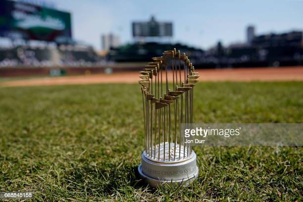 A replica World Series Trophy today's promotional giveaway on the field before the game between the Chicago Cubs and the Pittsburgh Pirates at...