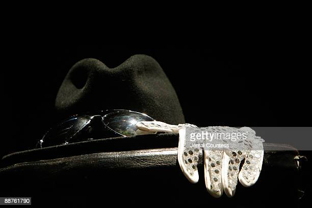 Replicas of Michael Jackson's trademark fedora sunglasses and sequined glove displayed on stage during a public tribute to Michael Jackson at The...