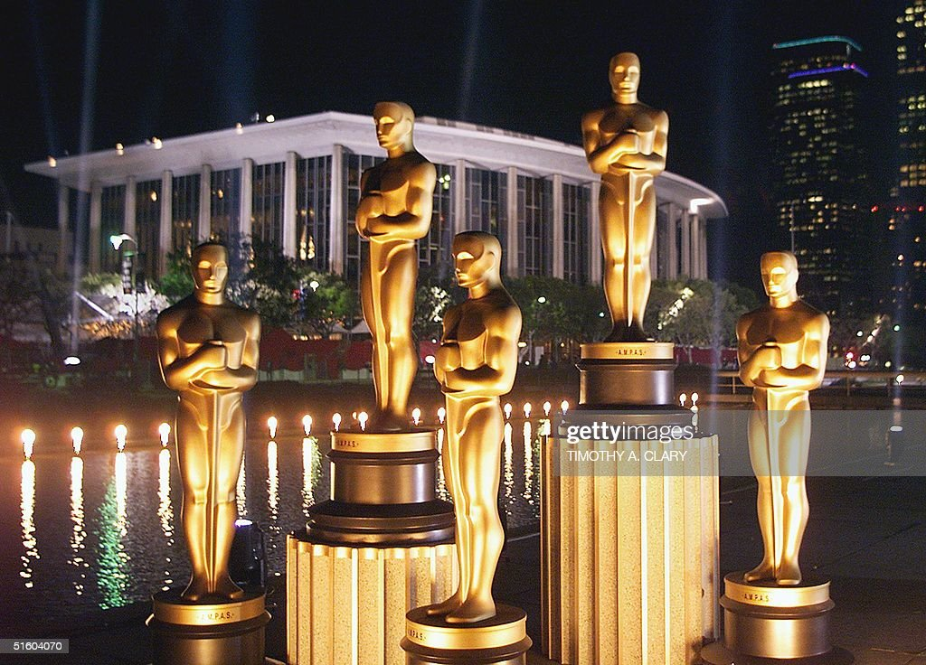 Replicas of Oscar statues are lit in the night outside the Dorothy Chandler Pavilion 19 March 1999 in Los Angeles ahead of the 71st Academy Awards to be held 21 March 1999 at the Pavilion. (ELECTRONIC IMAGE) AFP PHOTO/Timothy A. CLARY