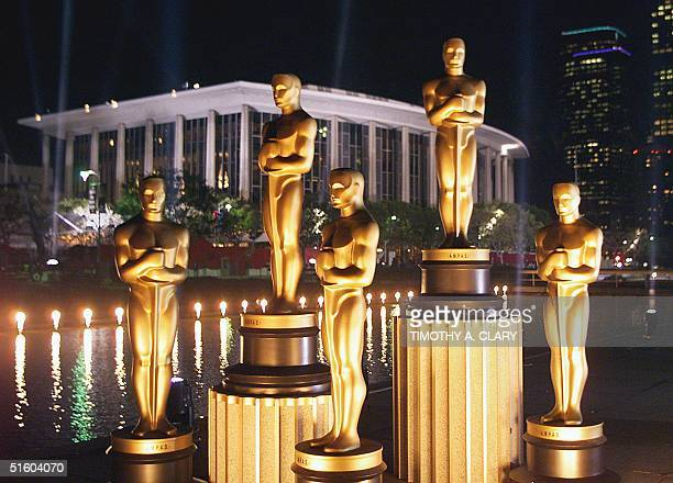 Replicas of Oscar statues are lit in the night outside the Dorothy Chandler Pavilion 19 March 1999 in Los Angeles ahead of the 71st Academy Awards to...