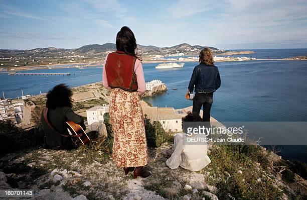 Report On The Island Of Ibiza Ibiza mars 1972 Quatre personnes de dos en tenues hippies jouent de la musique devant une prison en contrebas face à la...