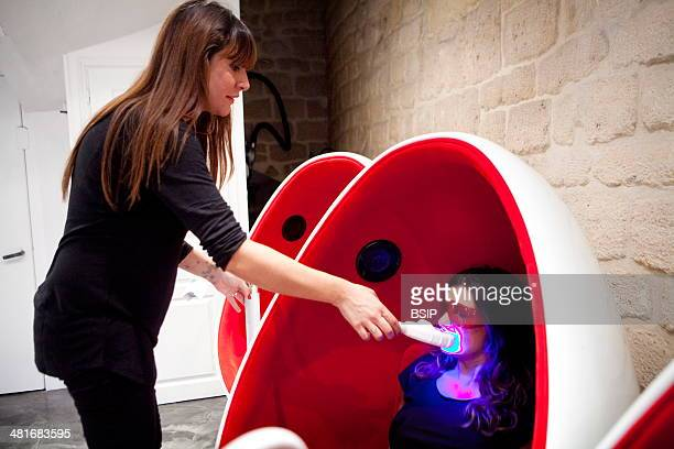 Reportage in a smile bar in Paris France Teeth whitening involves applying a whitening paste using a special mouthpiece then exposing the teeth to a...