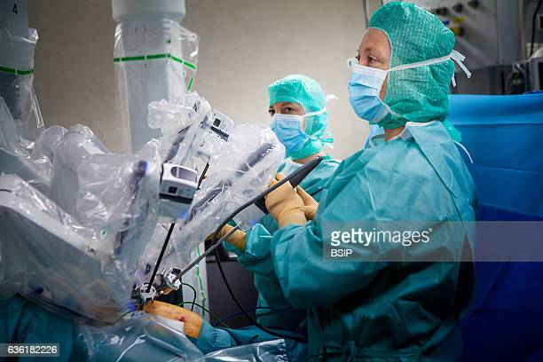 Reportage in an operating theatre during a hysterectomy using the da Vinci robot¬ A nurse and the surgeon position the robotÕs mechanical arm