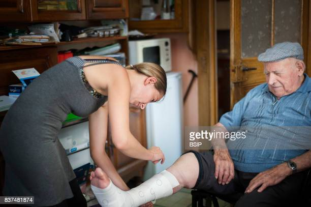 Reportage, in Haute-Savoie, France. Nurse travels her small mountain town daily to meet her patients, she treats a patient suffering from leg ulcers.