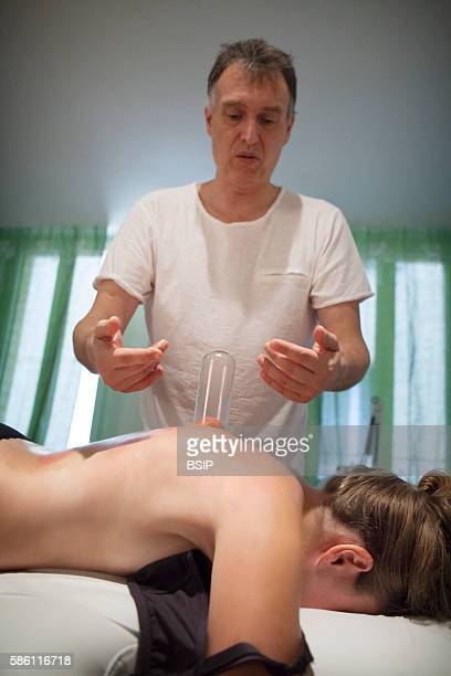 Reportage on a therapist who specializes in traditional Chinese medicine Applying cuppingglasses massages connective tissue and improves...
