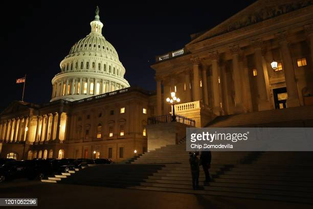 A reporter and camera operator work on the Senate steps during the first evening of President Donald Trump's impeachment trial January 21 2020 in...