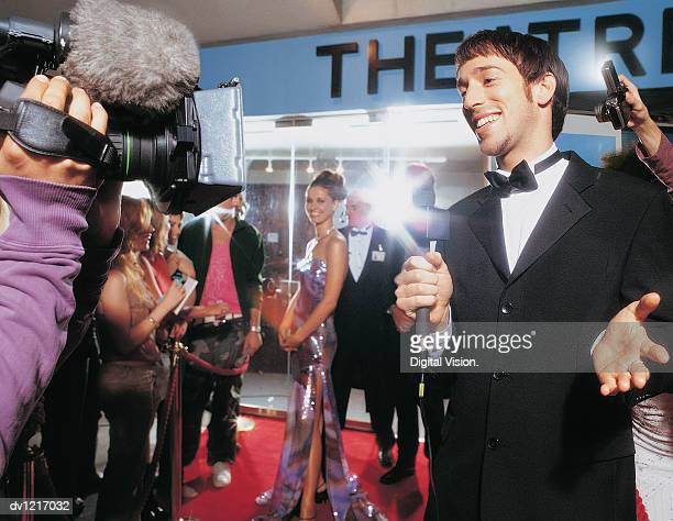 TV Reporter Being Broadcasted at a Film Industry Night in Front of a Crowd of People