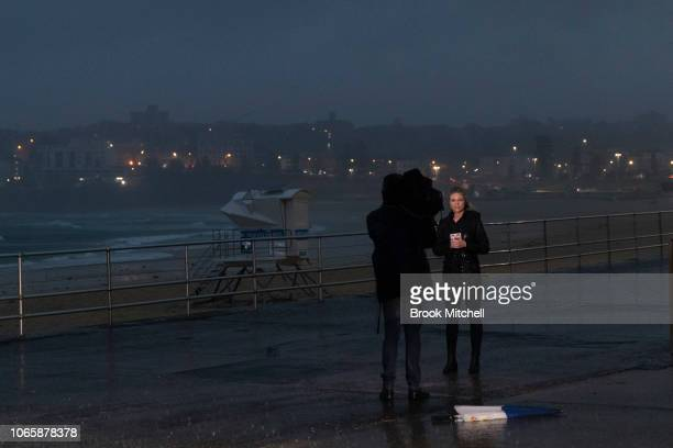 A reporter braves wild and wet weather at Bondi on November 28 2018 in Sydney Australia Two months worth of rain is expected to fall within a few...