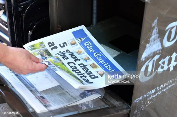 A reporter buys a Capital Gazette newspaper on June 29 in Annapolis Maryland A man armed with a shotgun and smoke grenades burst into the newspaper...