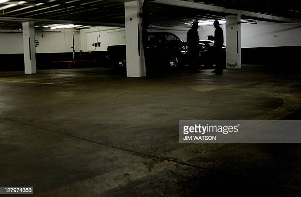 A reporter confers with a man in the shadows next to column 32 on D floor of the garage at 1401 Wilson Blvd 01 July 2005 in Rosslyn VA where...
