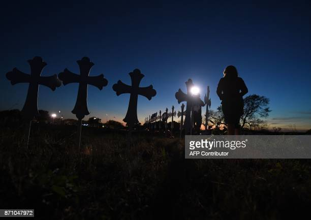 TOPSHOT A reporter does a report at a row of crosses for each victim after a mass shooting that killed 26 people in Sutherland Springs Texas on...