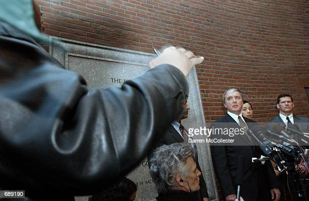 A reporter gestures while asking a question as US Attorney Michael Sullivan Assistant US Attorney Colin Owyang and FBI Special Agent in Charge...