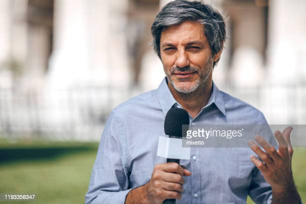 reporter holding microphone on the street - presenter stock pictures, royalty-free photos & images