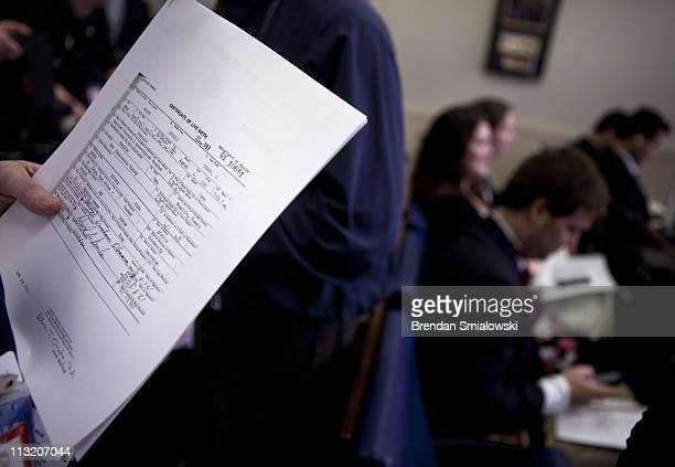 A reporter holds a copy of President Barack Obama's long form birth certificate in the Briefing Room of the White House April 27 2011 in Washington...