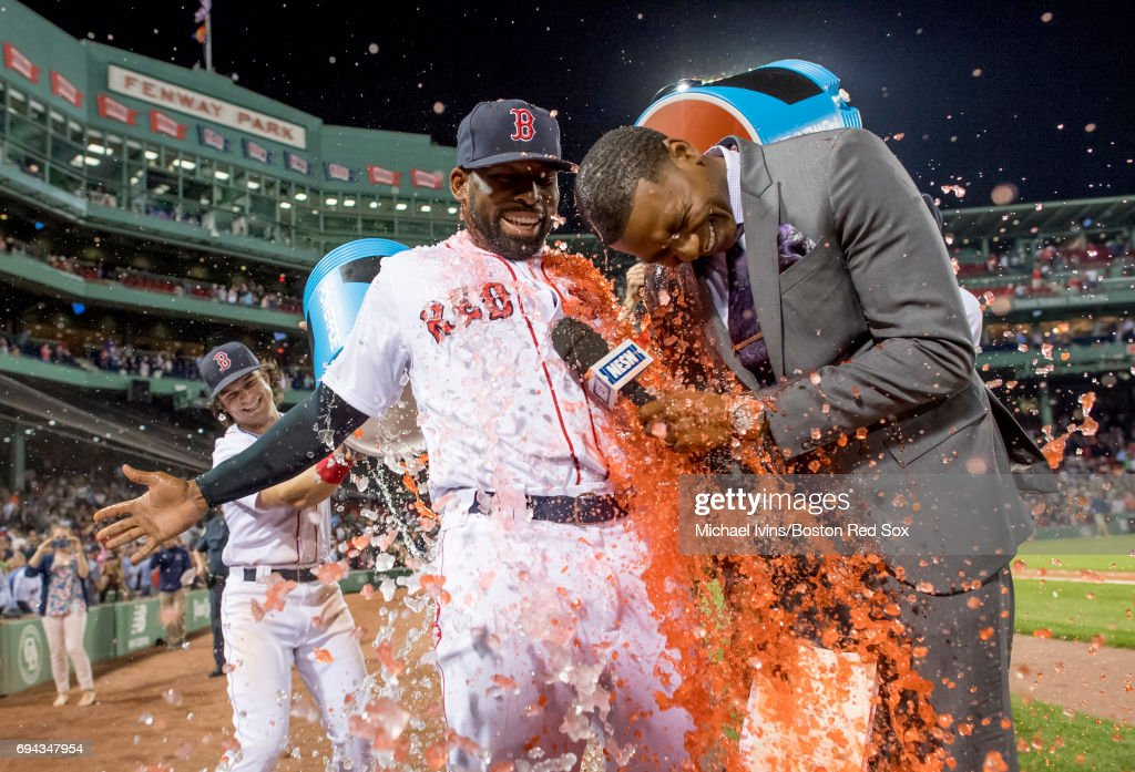 NESN reporter Jahmai Webster and Jackie Bradley Jr. #19 of the Boston Red Sox are doused after Bradley's two-run home run in the ninth inning led to a 5-3 win over the Detroit Tigers at Fenway Park on June 9, 2017 in Boston, Massachusetts.